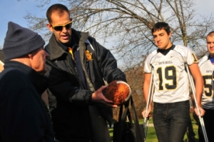 Coach Miller presenting a signed football to Steve Wanner.  Photo courtesy of Statesville Record & Landmark.