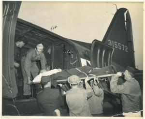 Tom Hudson (holding stretcher from above) assists a wounded soldier onto the plane.
