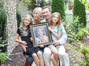 Lincoln Ely and his family hold a portrait of Erica.